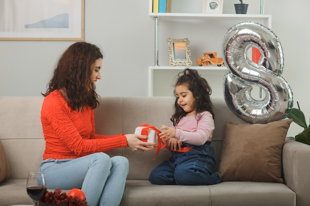 Madre feliz recibiendo regalo de su pequeña hija sentada en un sofá sosteniendo una tarjeta de felicitación sonriendo alegremente en la sala de estar iluminada celebrando el día internacional de la mujer el 8 de marzo