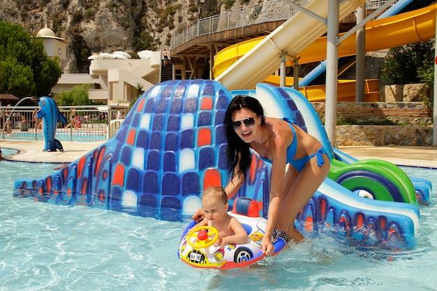 Madre feliz sonriente con un niño pequeño en la piscina en verano