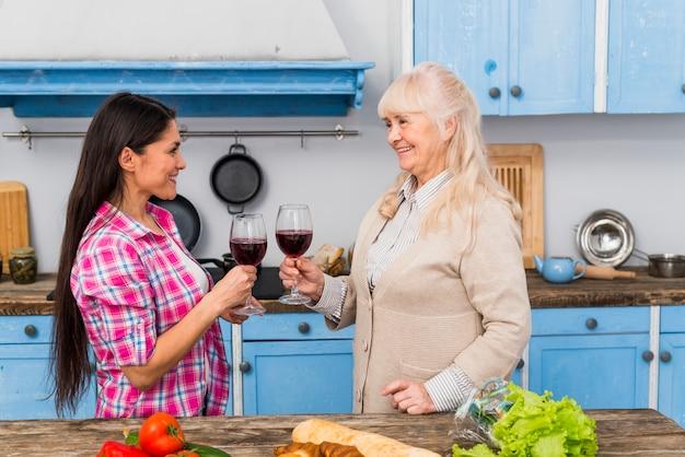 Madre feliz y su hija brindando copas de vino de pie detrás de la mesa