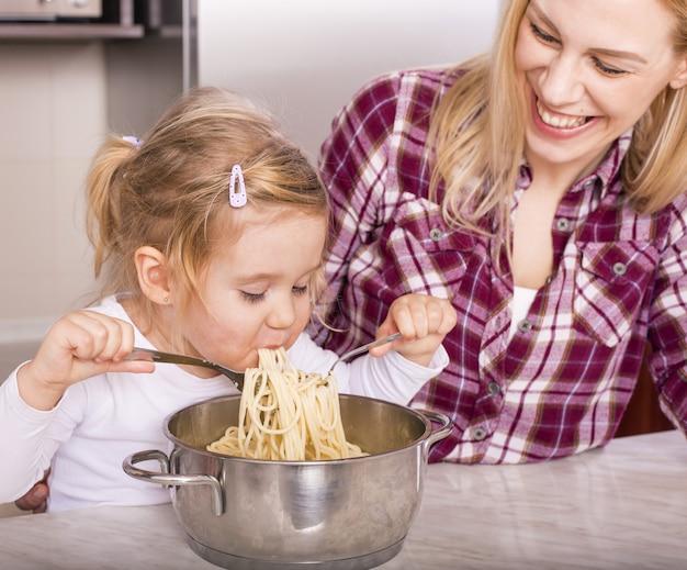 Madre feliz con su hija comiendo espaguetis caseros en la encimera de la cocina