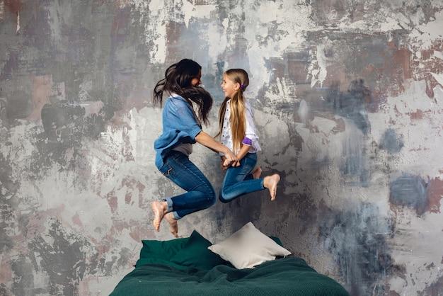 Madre feliz y su pequeña hija saltando en la cama cogidos de la mano