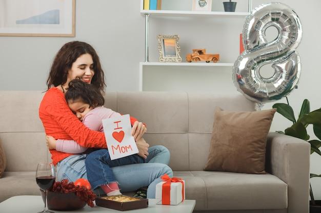 Madre feliz con su pequeña hija sentada en un sofá sosteniendo una tarjeta de felicitación sonriendo alegremente en la sala de estar iluminada celebrando el día internacional de la mujer el 8 de marzo