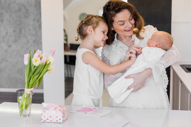Madre feliz con sus dos lindos niños de pie junto a la mesa blanca