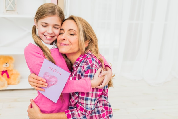 Madre feliz con la tarjeta de felicitación que abraza a la hija