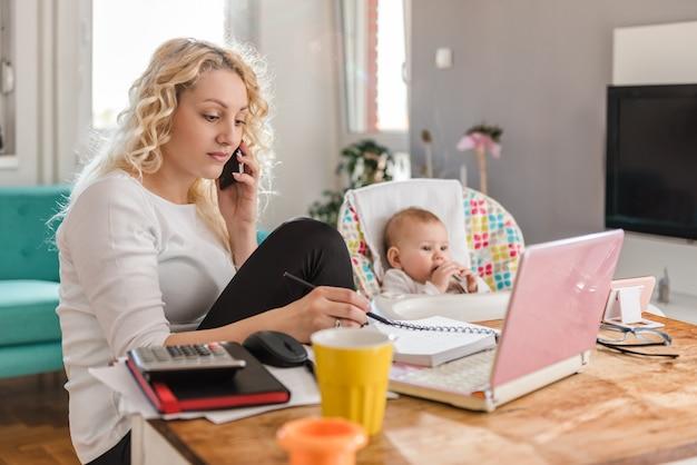 Madre hablando por teléfono inteligente en la oficina en casa