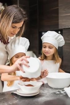 Madre haciendo comida en la cocina con sus dos hijas.