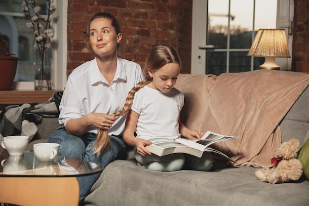 Madre haciendo trenzas en el cabello de su hija