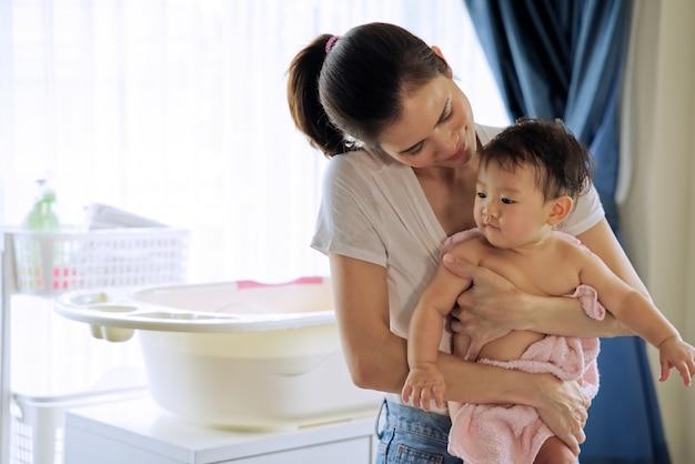 Madre hermosa asiática que celebra al pequeño bebé lindo después de tomar un baño y mirar y su niño que se coloca en el cuarto