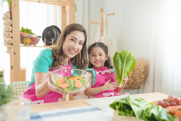 Madre hermosa e hija asiáticas que llevan el delantal rosado que cocina el desayuno en la cocina.