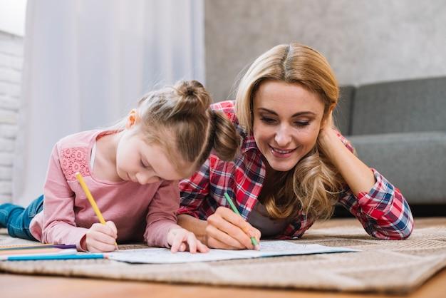 Madre hermosa e hija que dibujan junto en el libro en casa