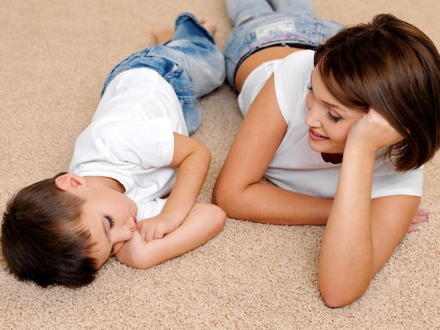 Madre hermosa y feliz al niño dormido que está tendido en el suelo