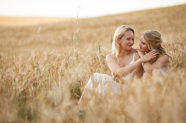 Madre con hermosa hija en un campo de otoño