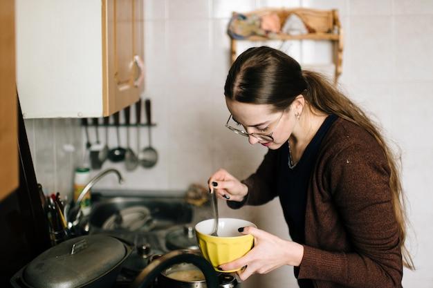 Madre hermosa joven de pelo largo que prepara la comida en la cocina para su hijo