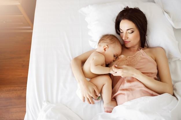Madre hermosa joven que amamanta a su bebé recién nacido que miente en cama en casa. desde arriba.