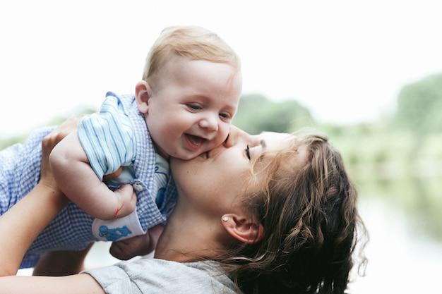 Madre hermosa joven que celebra al pequeño bebé lindo que sonríe