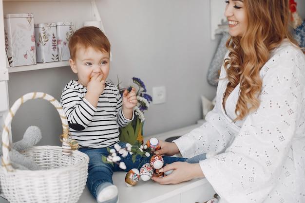 Madre hermosa con el pequeño hijo en una cocina