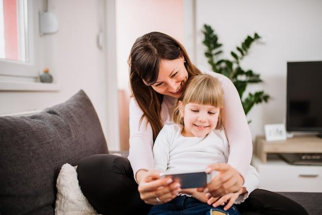 Madre hermosa que hace un selfie con su pequeña hija linda que usa un teléfono elegante.