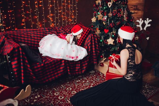 Madre en hermoso vestido negro y sombrero de santa claus con presente contra niño dormido en el sofá.