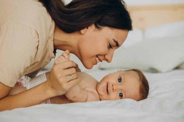 Madre con hija acostada en la cama
