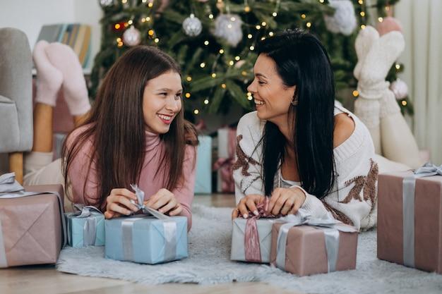 Madre con hija adulta con regalos de navidad por árbol de navidad