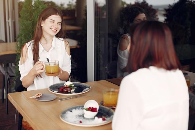 Madre con hija adulta sentada en un café