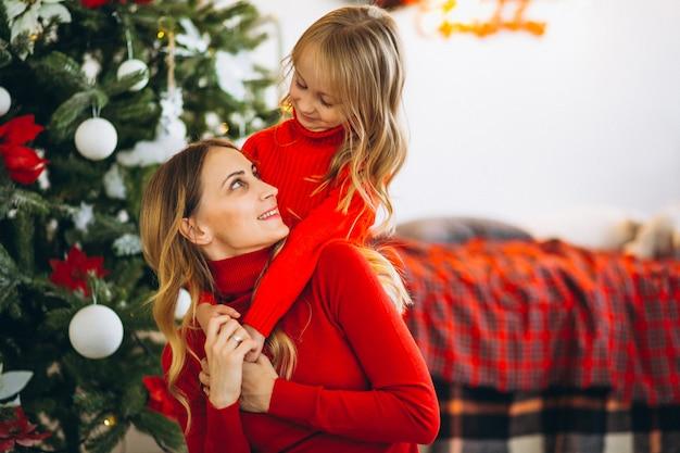 Madre con hija por arbol de navidad