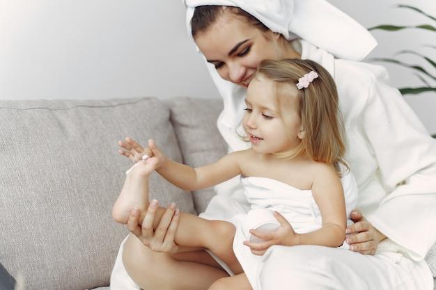 Madre con hija en bata de baño y toallas