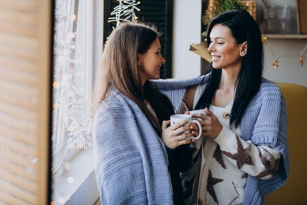 Madre con hija bebiendo té juntos en la cocina junto a la ventana
