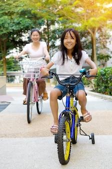 Madre y una hija en bicicleta en el parque