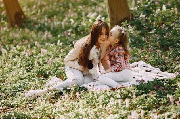 Madre con hija en un bosque de primavera con perro