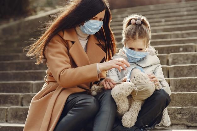 Madre con hija camina afuera en máscaras