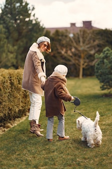 Madre con hija camina con un perro
