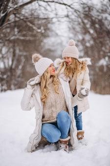 Madre con hija caminando juntos en un parque de invierno