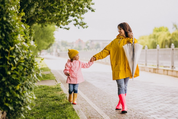 Madre con hija caminando en el parque bajo la lluvia con botas de goma