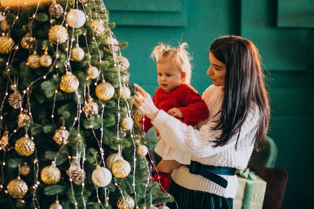 Madre con hija colgando juguetes en árbol de navidad