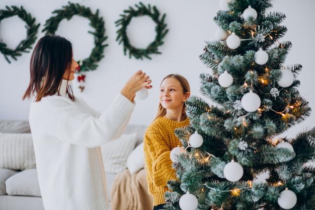 Madre con hija decorando el árbol de navidad