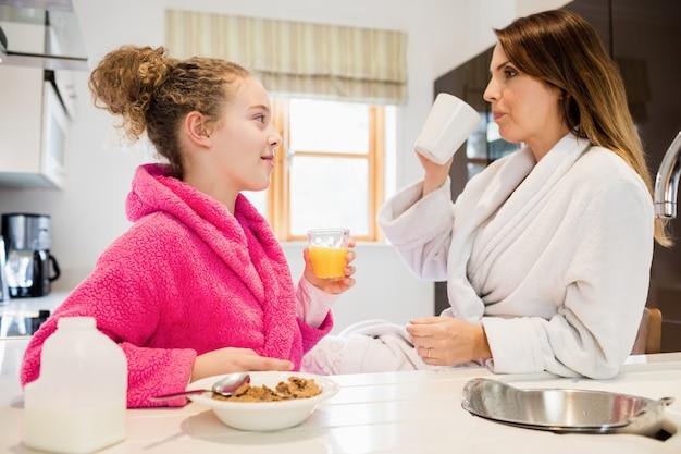La madre y la hija de desayunar en la cocina