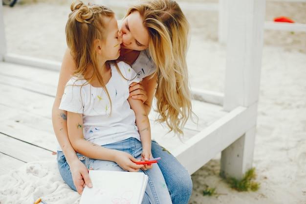 Madre con hija dibujando en un parque