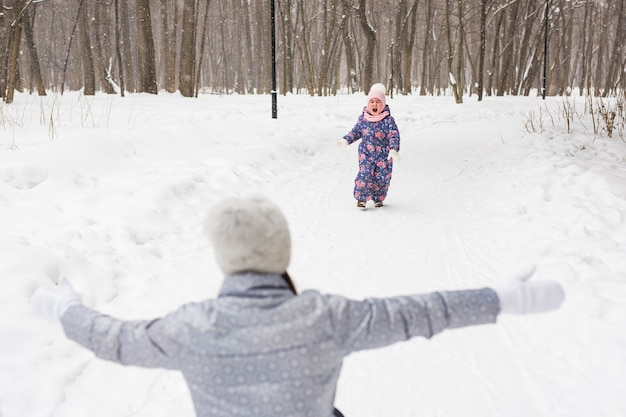 Madre con hija se divierten en el parque de invierno.