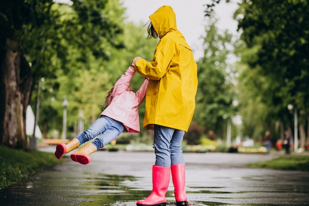 Madre con hija divirtiéndose en el parque en un clima lluvioso
