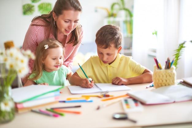 Madre, hija e hijo dibuja a lápiz sobre una hoja de papel sentado en su casa a la mesa en una habitación luminosa.