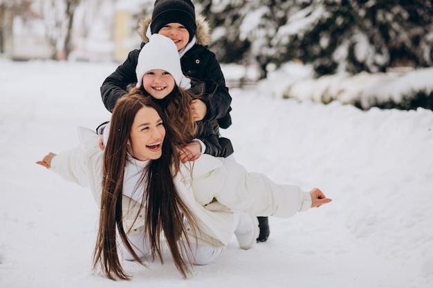 Madre con hija e hijo divirtiéndose en el parque lleno de nieve