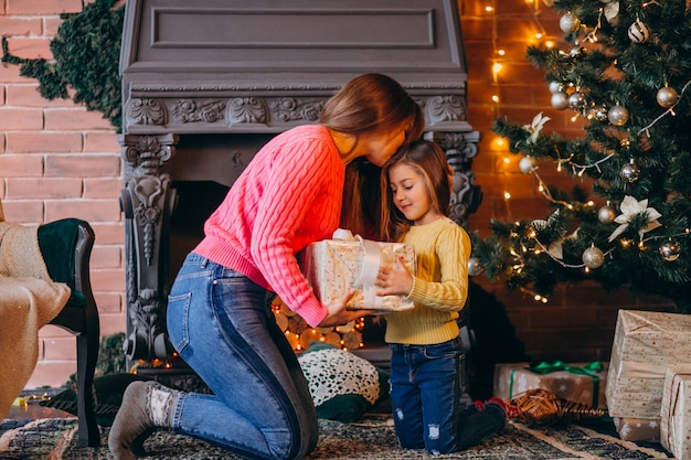 Madre con hija empacando presente por chimenea en navidad