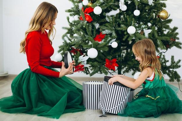 Madre con hija empacando regalos por arbol de navidad