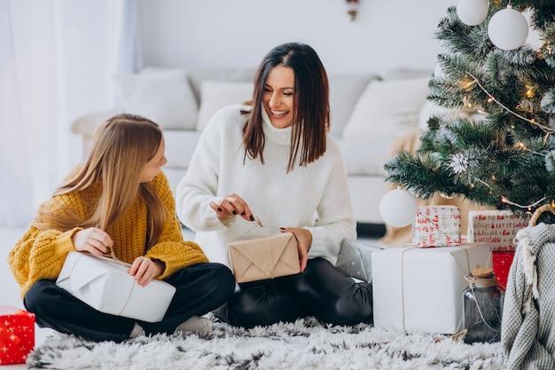 Madre con hija empacando regalos bajo el árbol de navidad