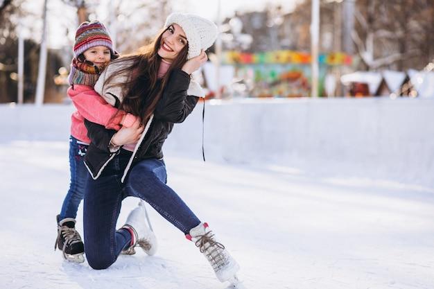 Madre con hija enseñando patinaje sobre hielo en una pista