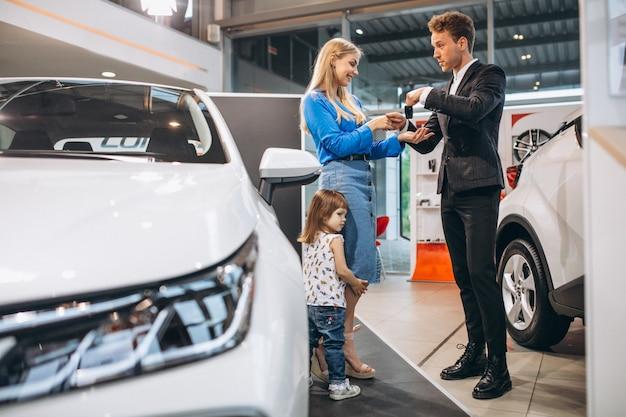 Madre con hija hablando con vendedor en una sala de exposición de automóviles