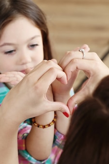 Madre con hija haciendo corazones con sus manos