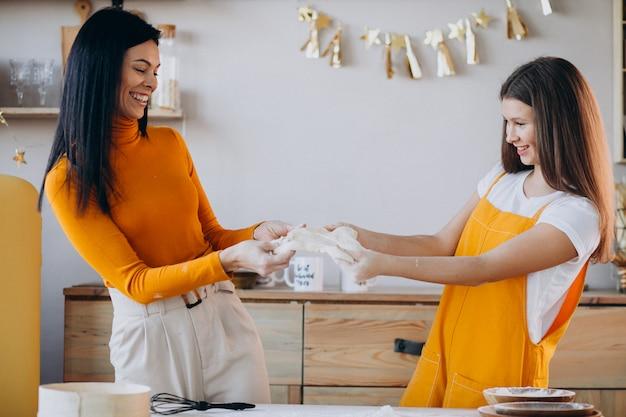 Madre con hija horneando en la cocina