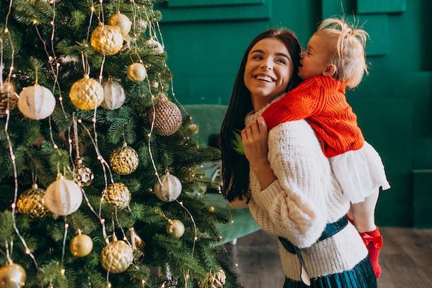 Madre con hija junto al árbol de navidad